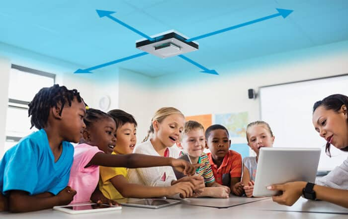 School children learning in a classroom with UV disinfection above them